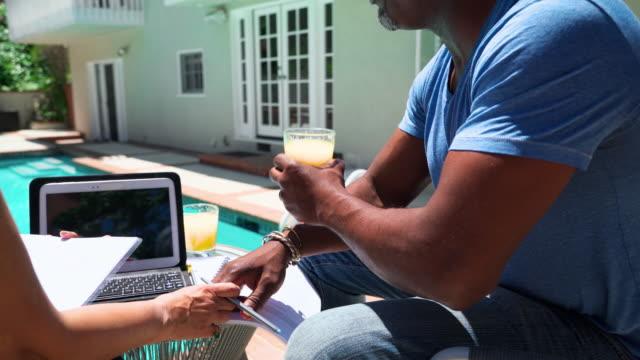 vidéos et rushes de le couple aîné, épouse et mari, assis en plein air à côté de la piscine, boire le jus d'orange, et parler de documents financiers et des investissements. caméra se déplaçant autour de la scène. - man drinking terrace
