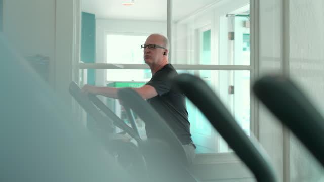 vídeos y material grabado en eventos de stock de el hombre mayor haciendo ejercicio de fitness en el gimnasio, utilizando la máquina de entrenamiento elíptico. - cabello corto
