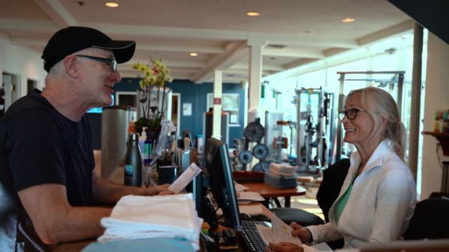 den seniora mannen pratar med senior kvinnan som arbetar i receptionen på gymmet. de båda skrattar. - gym skratt bildbanksvideor och videomaterial från bakom kulisserna
