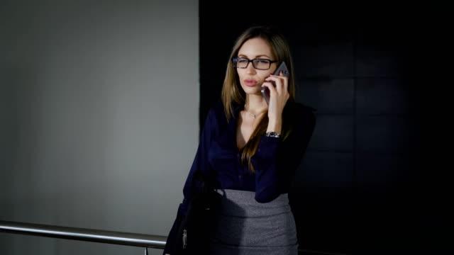 vídeos de stock, filmes e b-roll de o gerente sênior de edifício de escritórios. a mulher passa um tempo livre, falando por telefone. as conversações de garota no smartphone - saia