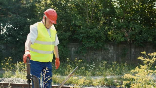 The senior railroader checks rails with repair mechanism of railway video