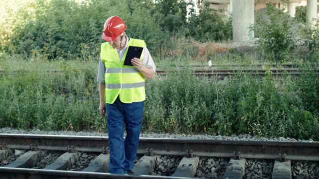 The senior railroader fixing data on the tablet when checking a track video