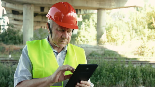 The senior railroader in uniform typing on tablet at camera at railway in summer video