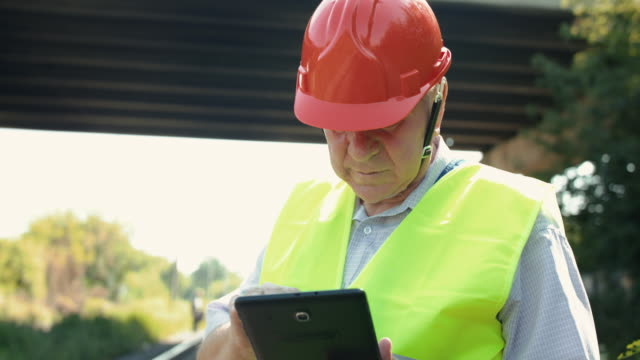 The senior railroader in uniform using tablet when checking a railway video