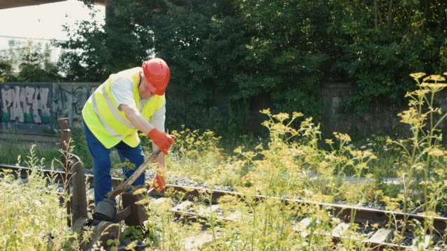 The senior railroader starts to use repair mechanism at railway in summer day video