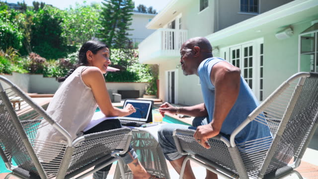 vídeos de stock e filmes b-roll de the senior retired couple, wife and husband, sitting outdoor next to the pool, drinking the orange juice, and talking about retirement plan and financial investments, using the printed documents and the tablet. - senior business woman tablet