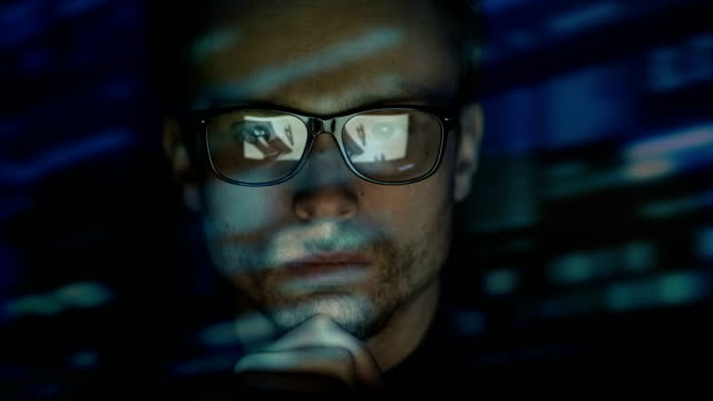 the serious man in glasses working near the screen. evening night time - отражение стоковые видео и кадры b-roll