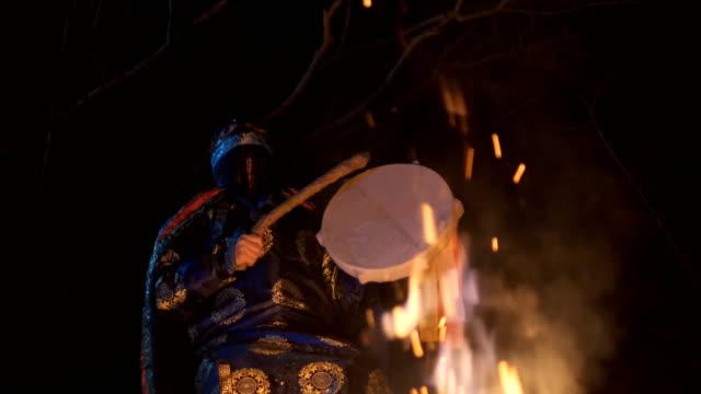 vidéos et rushes de le chaman est assis autour du feu et fait un rituel magique. - charmeur