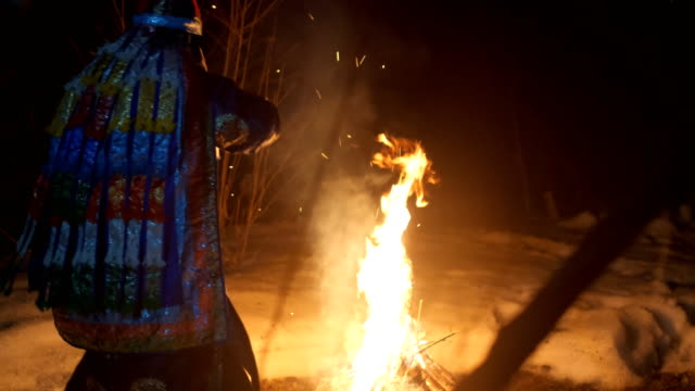 The shaman is sitting by the fire and sways, holding a tambourine in his hand. The shaman is sitting by the fire and sways, holding a tambourine in his hand. The shaman enters a trance. siberia stock videos & royalty-free footage