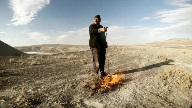 the shepherd warms tea on the fire the second man pushes dry grass on background dry mountainous area - mandriano video stock e b–roll