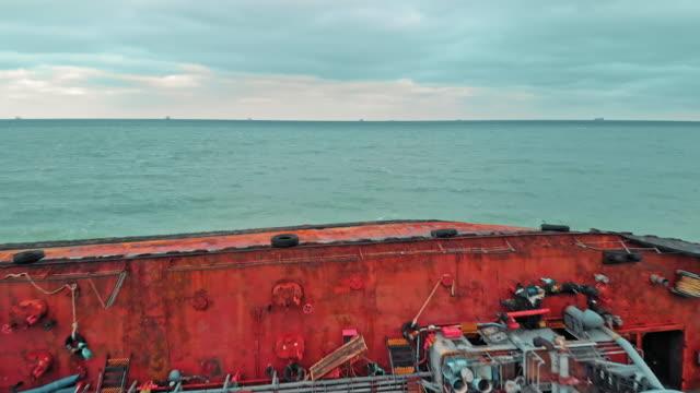 vídeos de stock, filmes e b-roll de o navio-tanque caiu em uma forte tempestade. a embarcação é virada de cabeça para baixo de seu lado por vazamento de combustível. tiro aéreo do zangão - navio tanque embarcação industrial