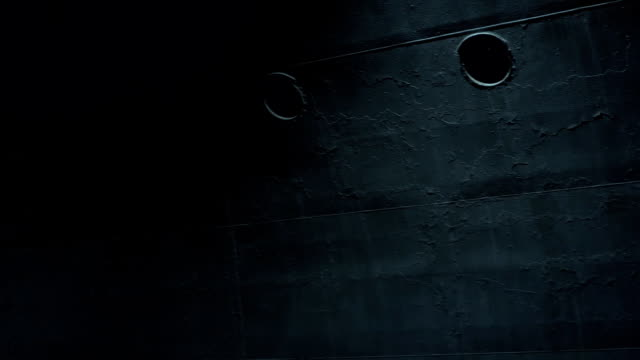 the side of the warship with windows, which is made of armored metal. part of a warship in night lighting. - quartiere generale video stock e b–roll