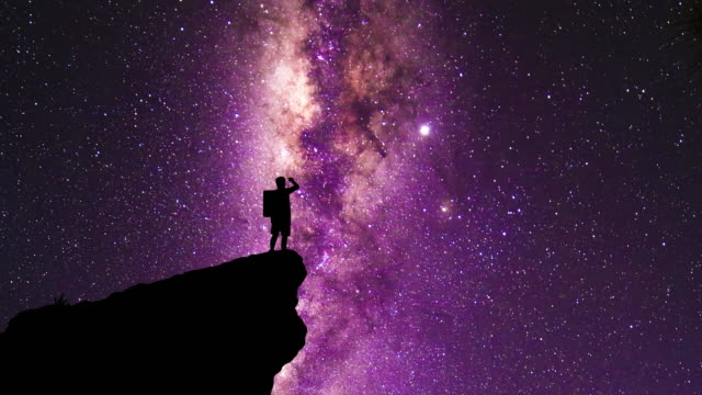 The silhouette of a backpacker standing on a cliff edge staring at the milky way and shooting stars