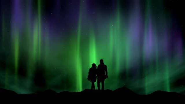 silhuetten av ett par tittar på aurora borealis och stjärnskott - polarklimat bildbanksvideor och videomaterial från bakom kulisserna