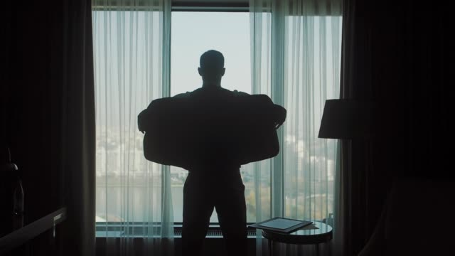 the silhouette of a man wearing a jacket in front of a window - giacca video stock e b–roll