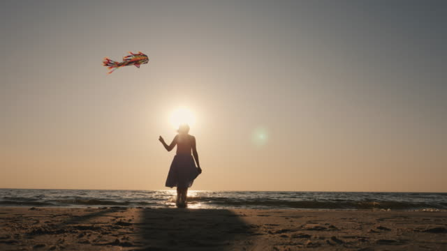 The silhouette of a young woman with a kite video