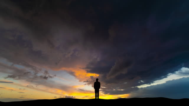 The silhouette of man on the cloud stream background The silhouette of man on the cloud stream background silhouette people stock videos & royalty-free footage