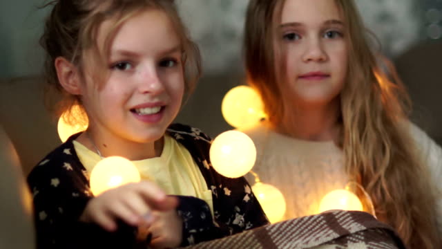 The sisters are covered by a blanket lying in bed with a garland of lights. Girlish friendship The sisters are covered by a blanket lying in bed with a garland of lights. Girlish friendship cousin stock videos & royalty-free footage