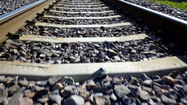 vídeos y material grabado en eventos de stock de las pequeñas rocas negras en la vía del ferrocarril de metal - aleación