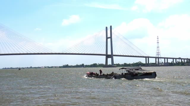 The small boat or barge glides through the river The small boat or barge glides through the river beneath the newly completed giant cable stayed bridge showing the development of traffic in the Mekong Delta region of Vietnam. suspension bridge stock videos & royalty-free footage