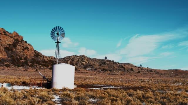 vídeos de stock e filmes b-roll de the small wind-powered water pump in colorado, usa - cisterna água parada