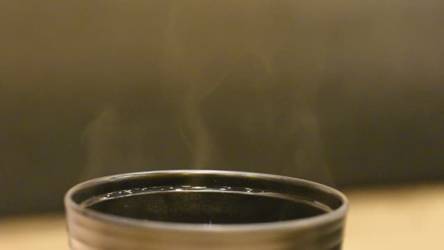 The smoke from the heat of the soup on the cup black.