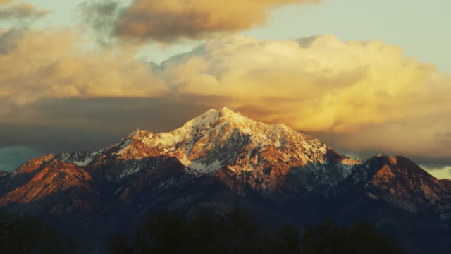 the snowcapped wasatch mountains above salt lake city, ut at sunrise/sunset with a dramatic cloudscape - utah video stock e b–roll