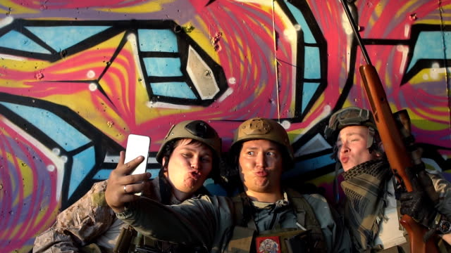 The soldiers are doing selfie on smartphone. Airsoft Game video