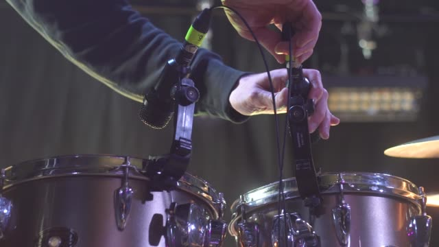 The sound technician tunes the drums and hangs up the microphones before the concert video