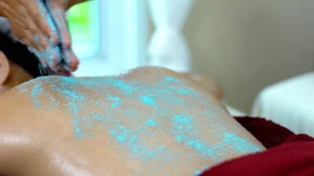 The spa terapist used spa salt on back of beautiful woman video