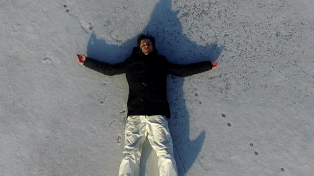 The spirit rises to heaven. The man is lying on the snow and resting.The spirit rises to heaven. philosophy stock videos & royalty-free footage