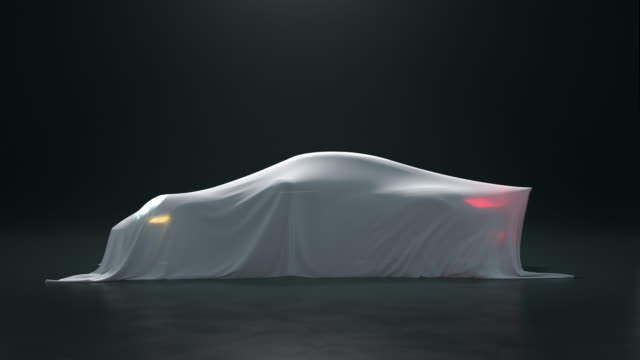 the sport car is covered with a white cloth on a black background. the fabric falls from the vehicle but under it is nothing. - coprire video stock e b–roll