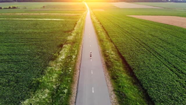 vídeos de stock, filmes e b-roll de o esportista rodando em uma estrada rural. quadrocopter tiro - fazendo cooper
