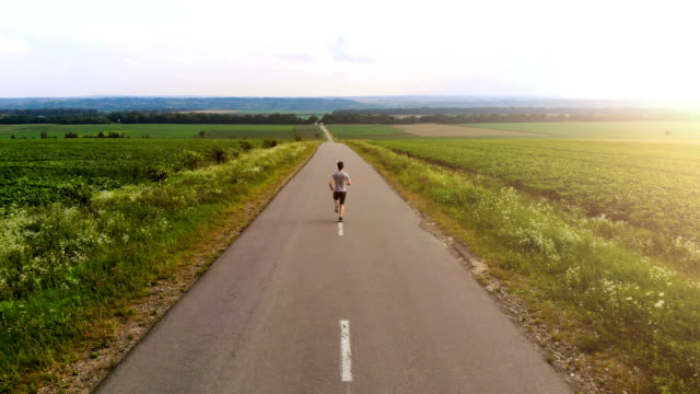 The sportsman running on the road on the sunset background. quadrocopter shot