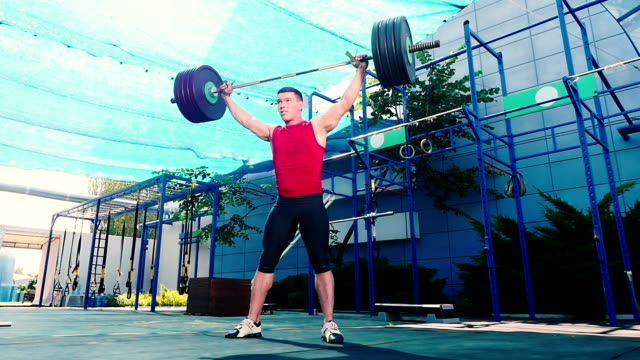 The sportsman throw down the barbell on the sports ground video