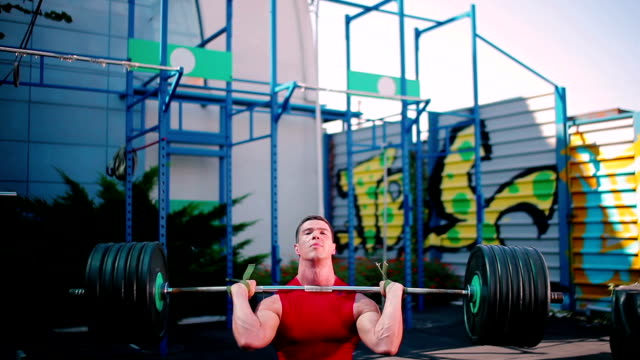 The sportsman training with barbell outdoor video