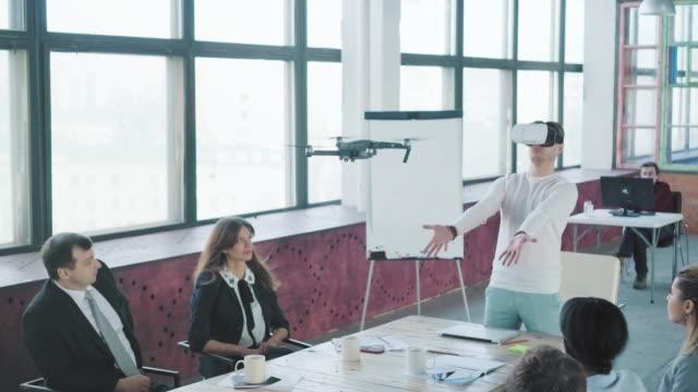 スタートアップチームは、ジェスチャーやバーチャルリアリティメガネを通じてドローンを管理する新しい技術をテストしています。成功。従業員は手をたたいてお互いを祝福します。コワ� ビデオ
