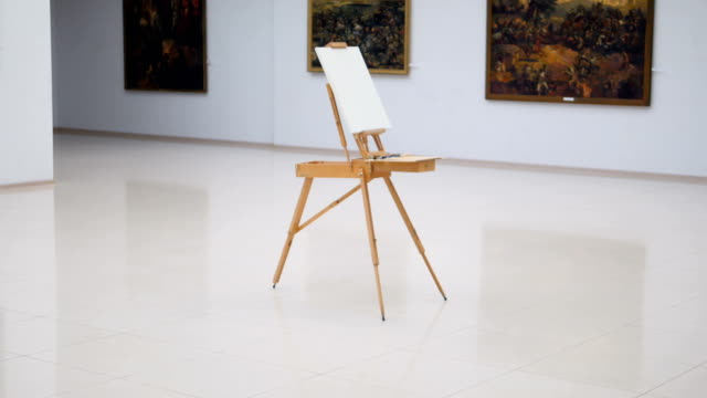 The steadicam shooting of the easel with white canvas on it. It is standing in the center of the gallery. 4K. video