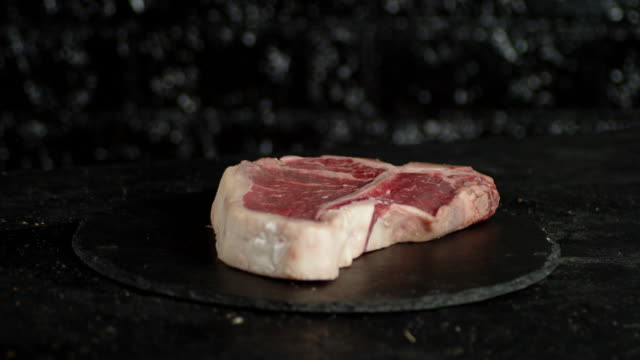 The steak raw t-bone on the stone board slowly rotates.