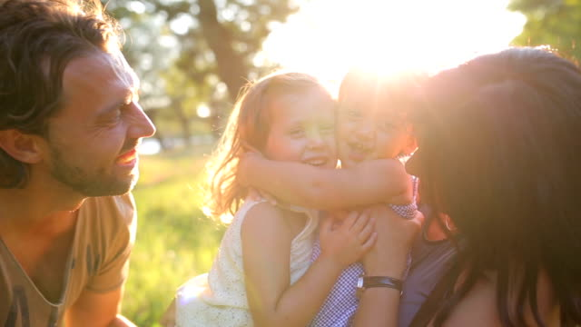 The story of a happy family Happy family on the nature of the summer, mother, father and children two sisters hugging.Sunset hug stock videos & royalty-free footage