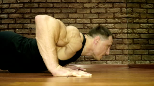 The strong man push up from the floor in the fitness center Young man pushes up from wooden floor in gym bodyweight training stock videos & royalty-free footage