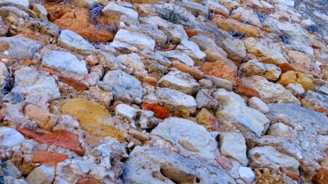 vídeos de stock e filmes b-roll de the structure of an ancient stone wall of various cobblestone - ivy building
