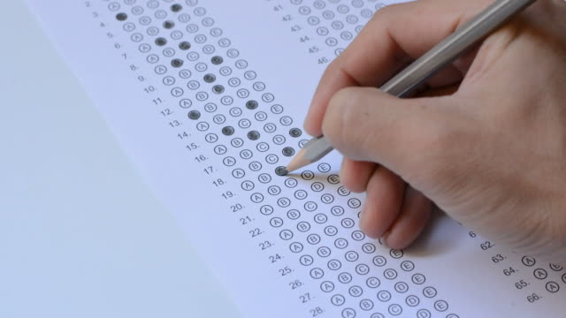 the student fills in answers on the standardized multiple choice test - esame università video stock e b–roll