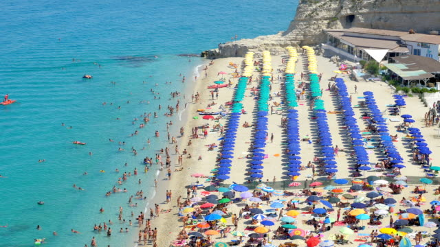 the summer beach, crowded and full of umbrellas - video di tropea video stock e b–roll