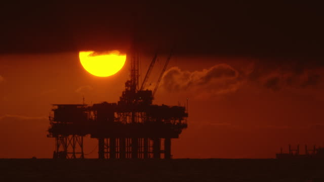 The Sun Peeks out from underneath Storm Clouds with a Silhouette of an Offshore Oil Drilling Rig Platform in the Foreground and an Oil (Petroleum) Tanker in the Background at Sunset underneath a Dramatic, Stormy Sky