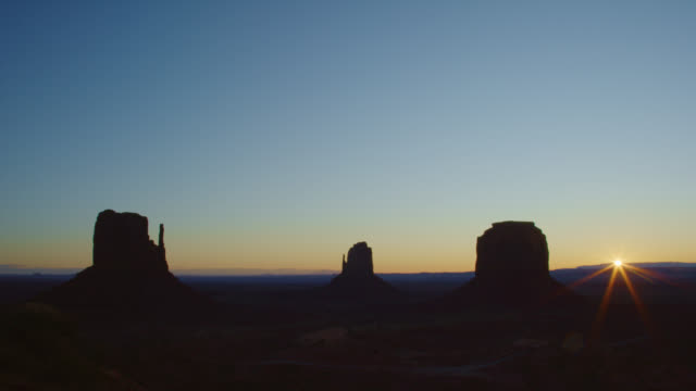 The Sun Rises Above the Horizon with Large Rock Formations in Silhouette in the Monument Valley Desert in Arizona/Utah at Sunrise/Sunset on a Clear Day