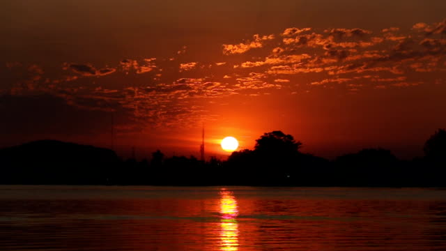 The sun rising over the horizon over the river.