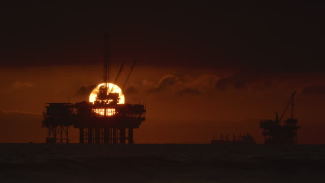 The Sun Sets on the Horizon with Silhouettes of Several Offshore Oil Drilling Rig Platforms and an Oil (Petroleum) Tanker in the Distance under a Dramatic, Stormy Sky