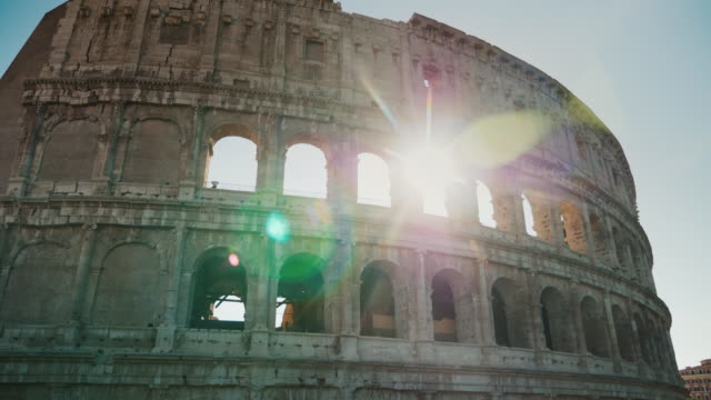 The sun shines beautifully through the arches of the Colosseum in Rome. Steadicam shot