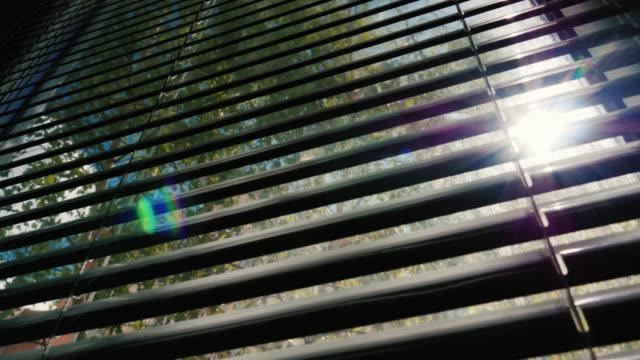 słońce świeci przez pół-zamknięte rolety na oknie - store filmów i materiałów b-roll
